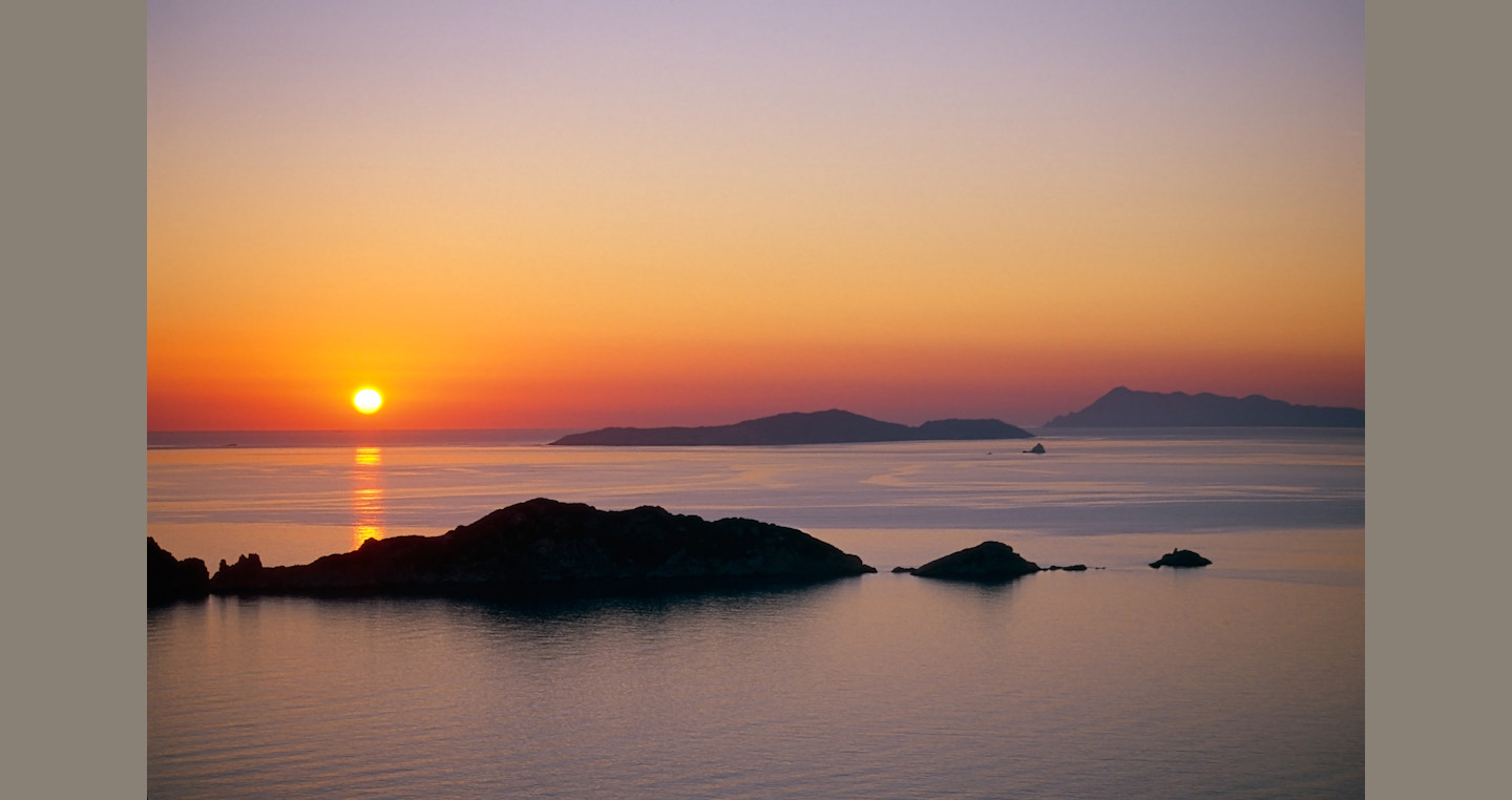 Receding islands are silhouetted against a calm orange lit sea