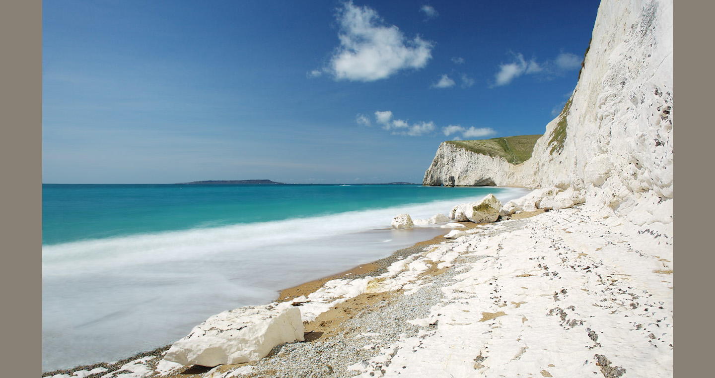 Sunlit white cliffs and wave contrast with blue water and sky