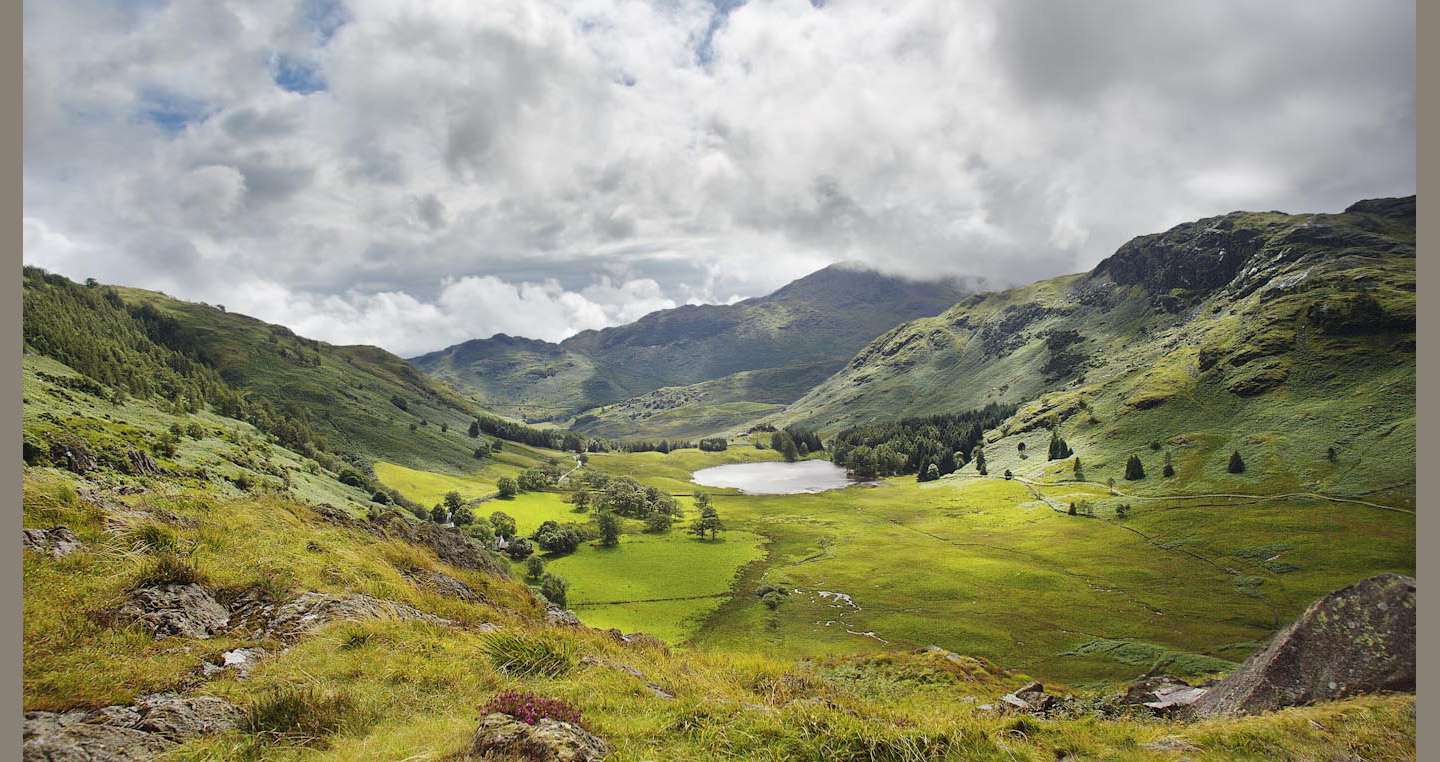 Mountains meadows and clouds encircle Blea Tarn