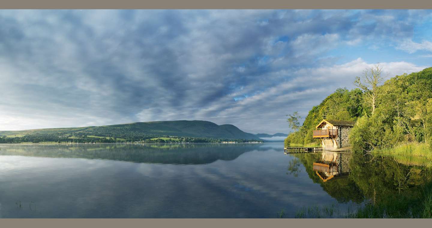 Boathouse and clouds reflect in the ephemeral still of Ullswater