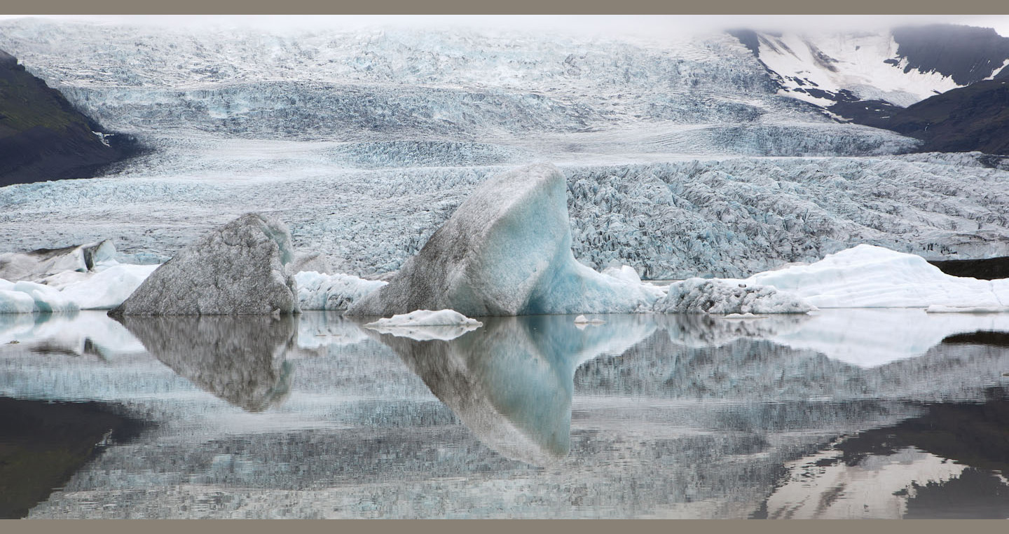 Blue and white icebergs reflected in the lagoon