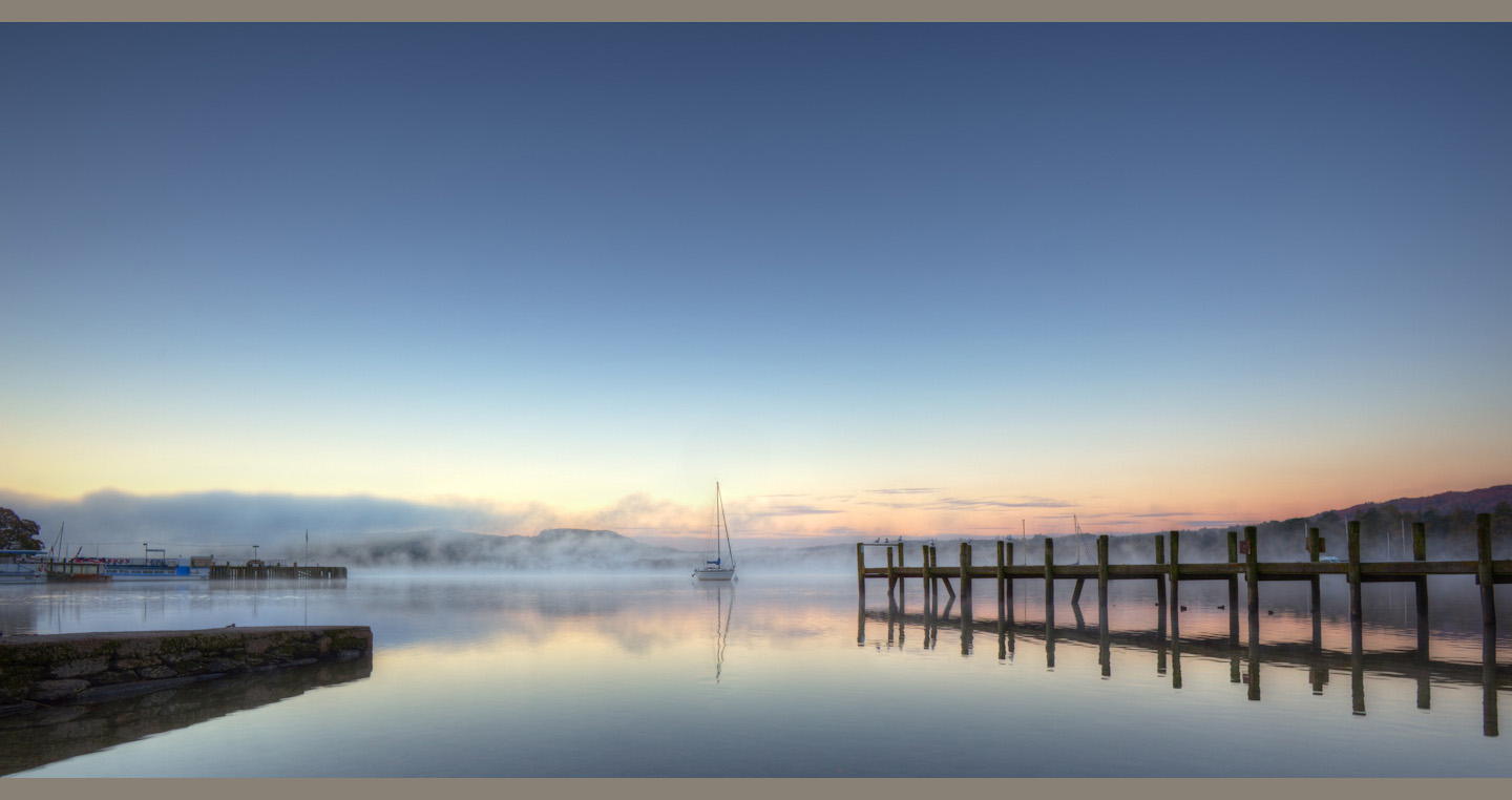 Wooden pier opposite low stone jetty point towards a yacht in misty pink dawn water